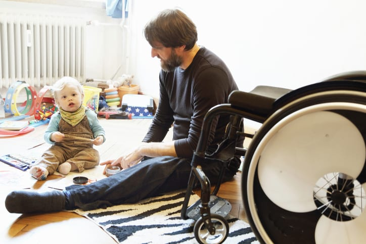 Law Office of Tipton-Downie Disabled father with son playing on floor